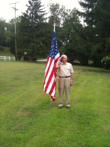 Dad in the front yard saluting.